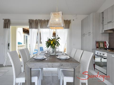 Dining table right next to the fully equipped and modern kitchen