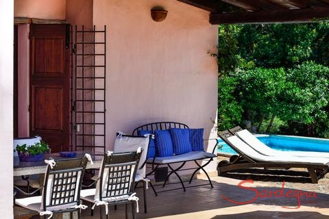 Shaded terrace equipped with dining table, bench and sunbeds by the pool