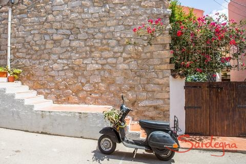 Vespa parked in front of an old stone house and a blooming bougainvillea in Santa Teresa di Gallura